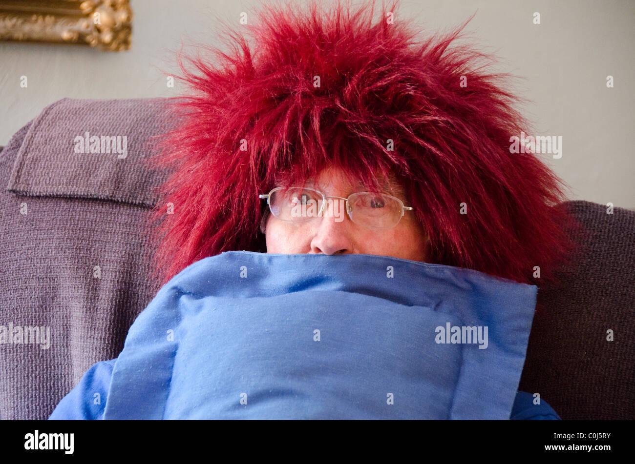 Un uomo anziano agisce silly mettendo su una rossa parrucca fuzzy. Stati Uniti d'America Foto Stock