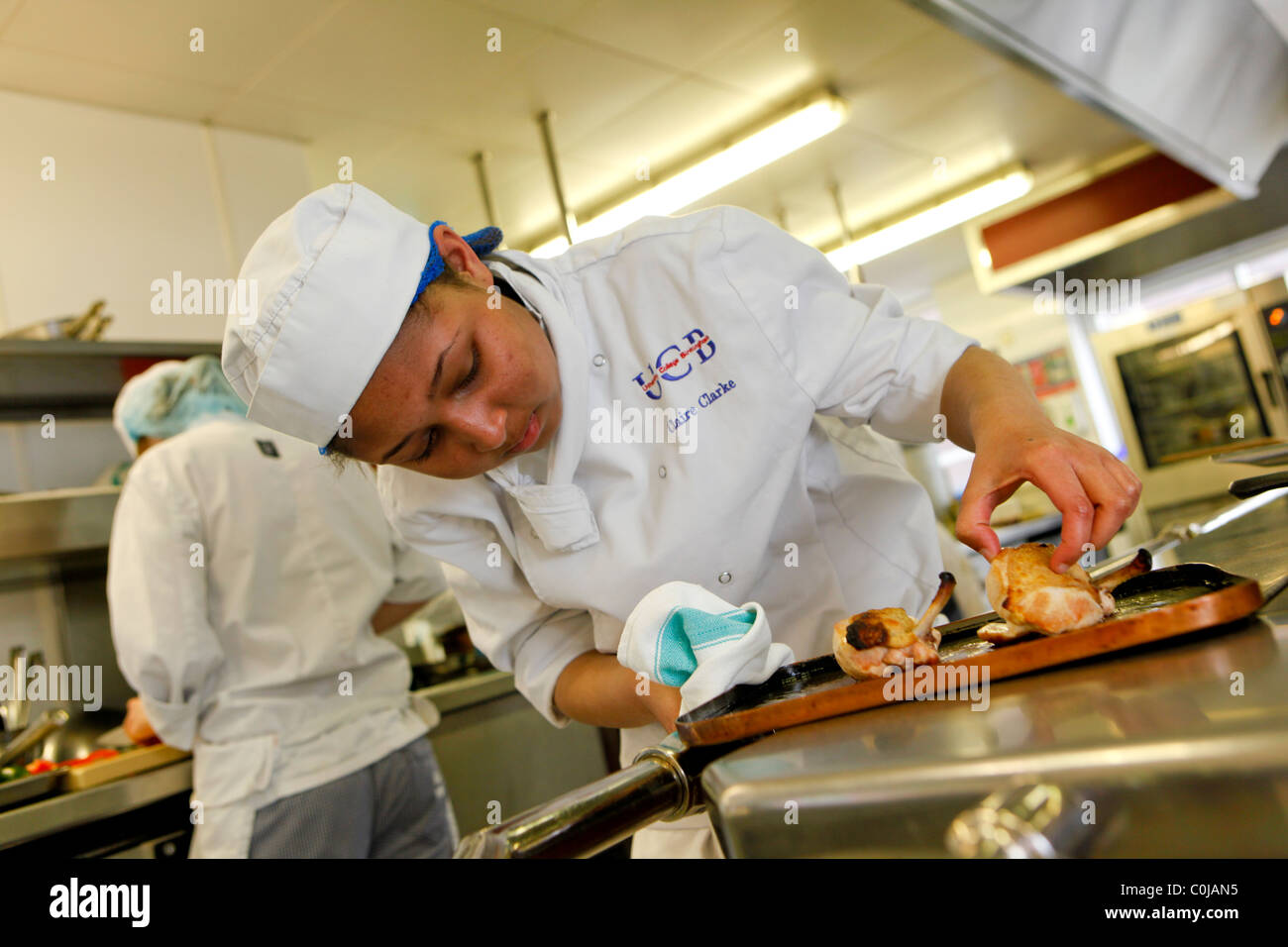 Chef in cucina a preparare il cibo in un college per ulteriori e istruzione superiore Immagini Stock