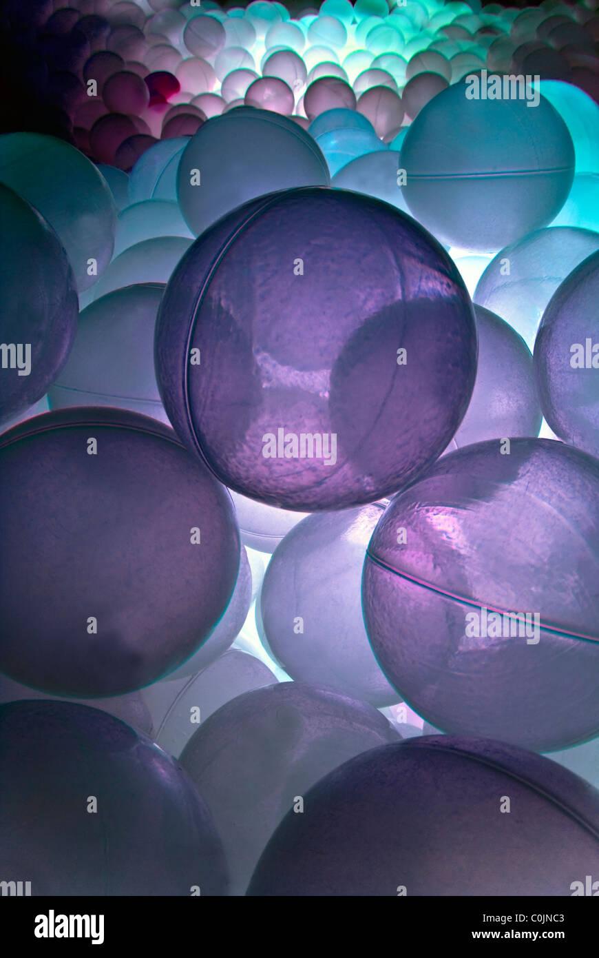 Piscina di palline con luce viola nella luminosa sala sensoriale. Foto Stock