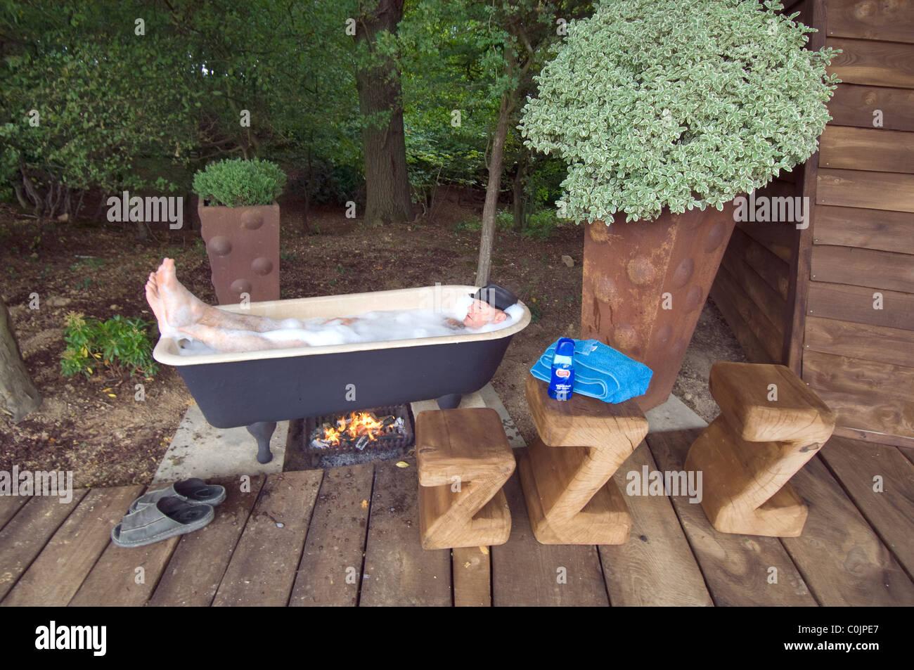 Vasca Da Bagno Esterna : Luomo rilassante nel suo alimentate a carbone con vasca da bagno