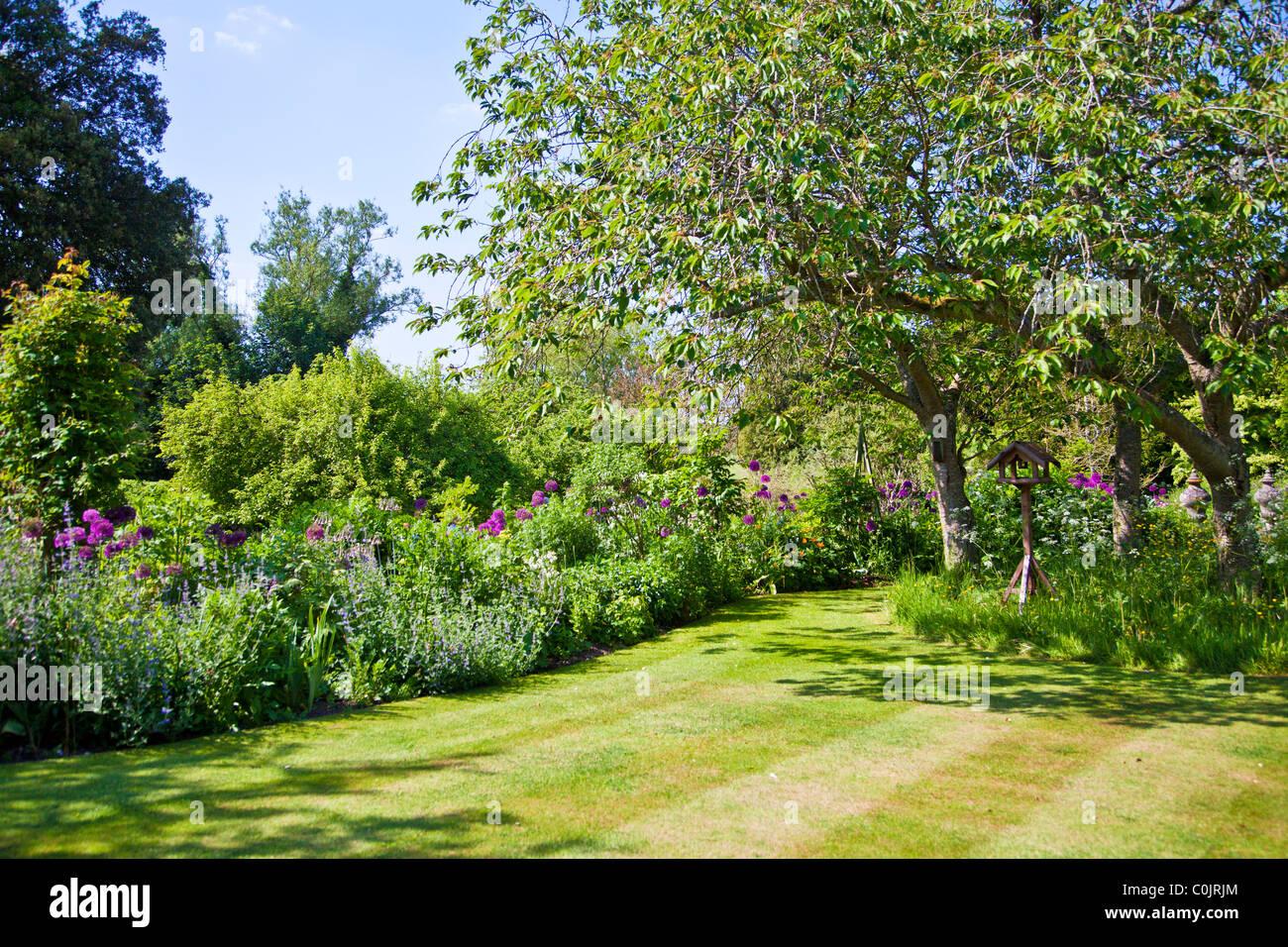 Aiuole o letti attorno un prato stripey in un paese di lingua inglese giardino in estate con legno bird tabella riportata sotto gli alberi. Foto Stock