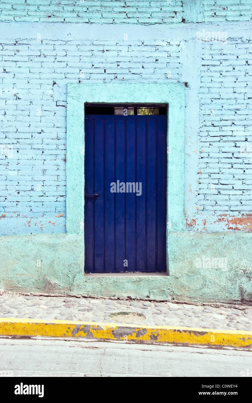 Il cerulean blu dipinto di un muro di mattoni con Deep Blue Door marciapiede di pietra e di colore giallo brillante Immagini Stock