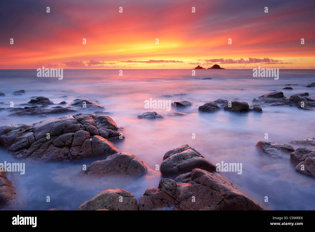 Un fantastico tramonto dipinge il cielo con colori gloriosi come lisce come la seta mare lambisce le rocce a Porth Immagini Stock
