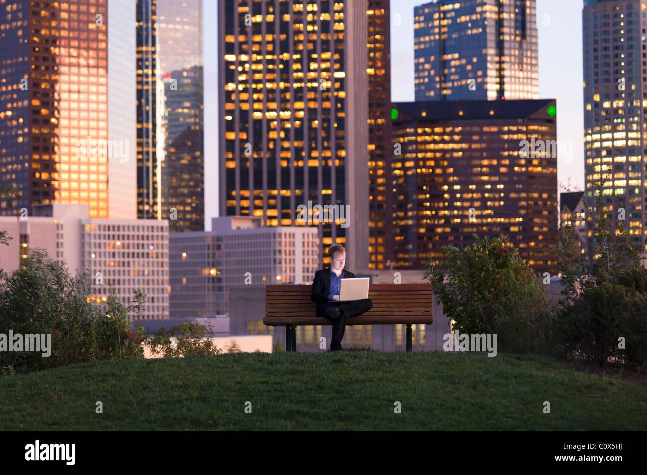 Voce maschile seduto su una panchina nel parco lavorando sul computer portatile con Los Angeles skyline della città Immagini Stock