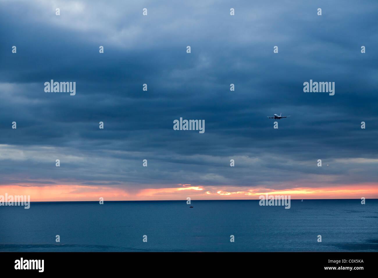 Aeromobile jet del passeggero sbarco oltre oceano contro nuvoloso cielo drammatico. Dockweiler Beach a Los Angeles, Immagini Stock