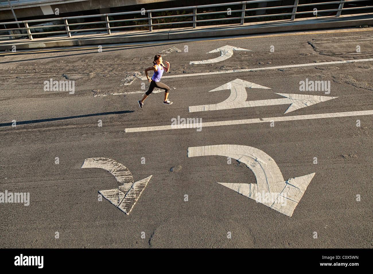Femminile in esecuzione sulla città urbana street bridge, cavalcavia con frecce direzionali dipinta sul marciapiede Immagini Stock