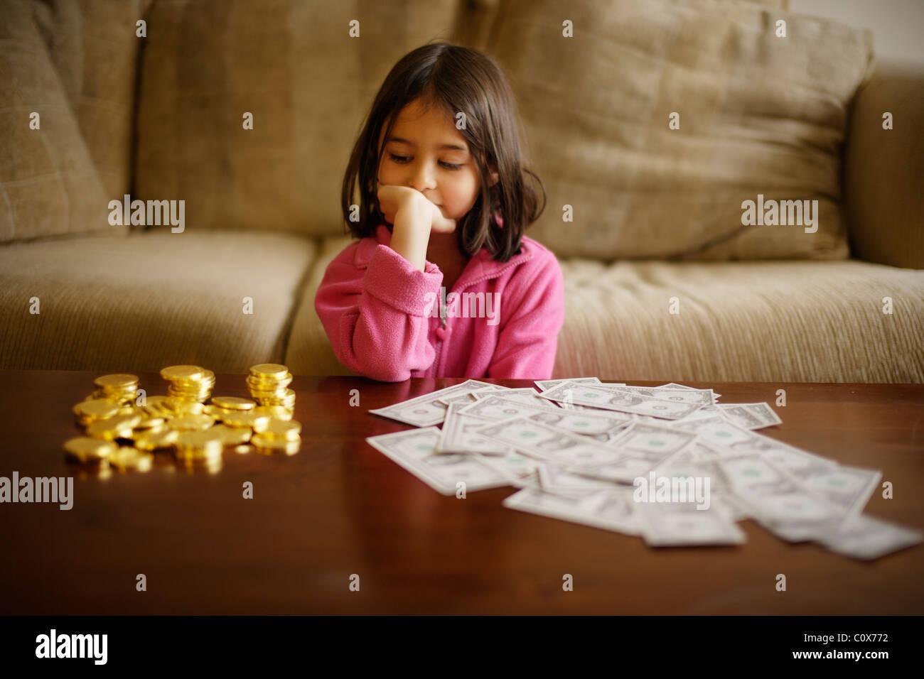Ragazza rende la decisione di investimento tra il cioccolato monete d oro e carta dollari USA Immagini Stock