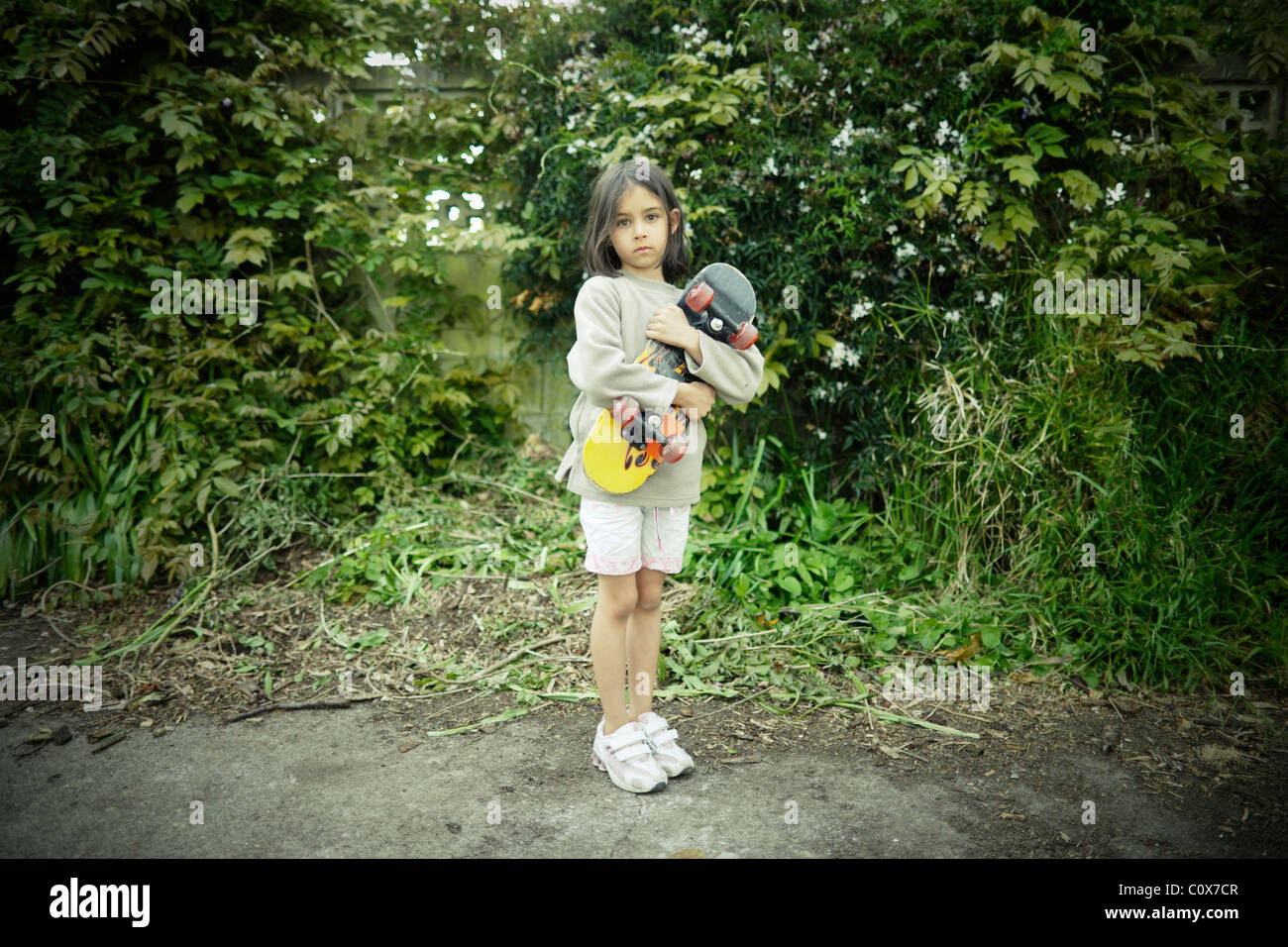 Ritratto di ragazza con lo skateboard. Immagini Stock
