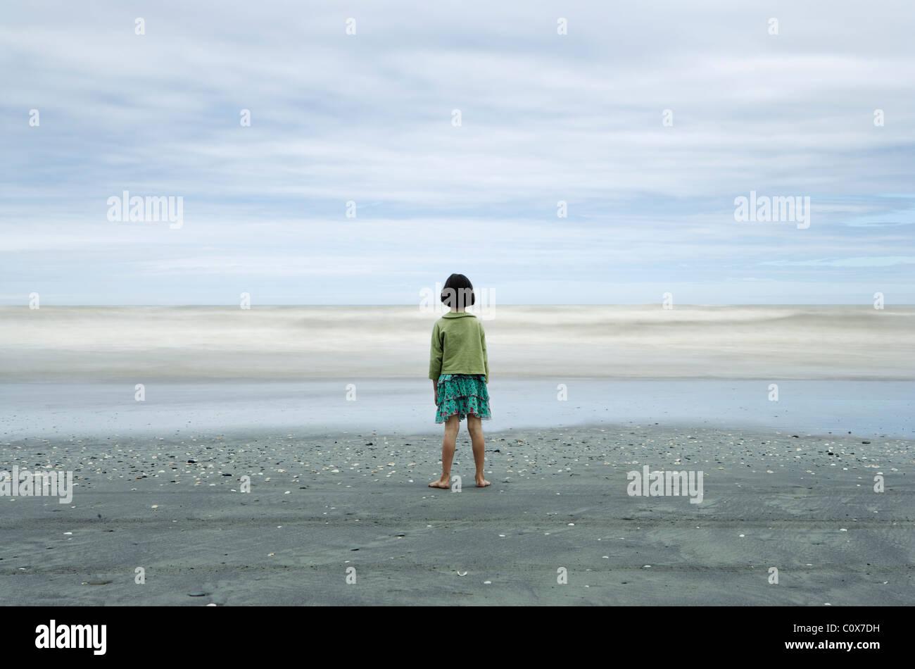 La ragazza di una messa a fuoco nitida guarda al mare con onde offuscata dalla lunga esposizione; sabbia nera vulcanica, Immagini Stock