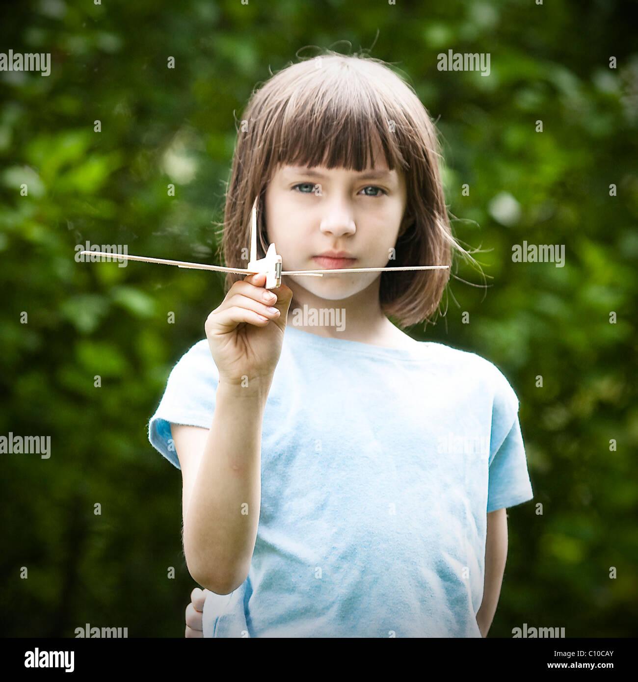 Una ragazza di 10 anni in possesso di un giocattolo di legno di balsa piano. Immagini Stock