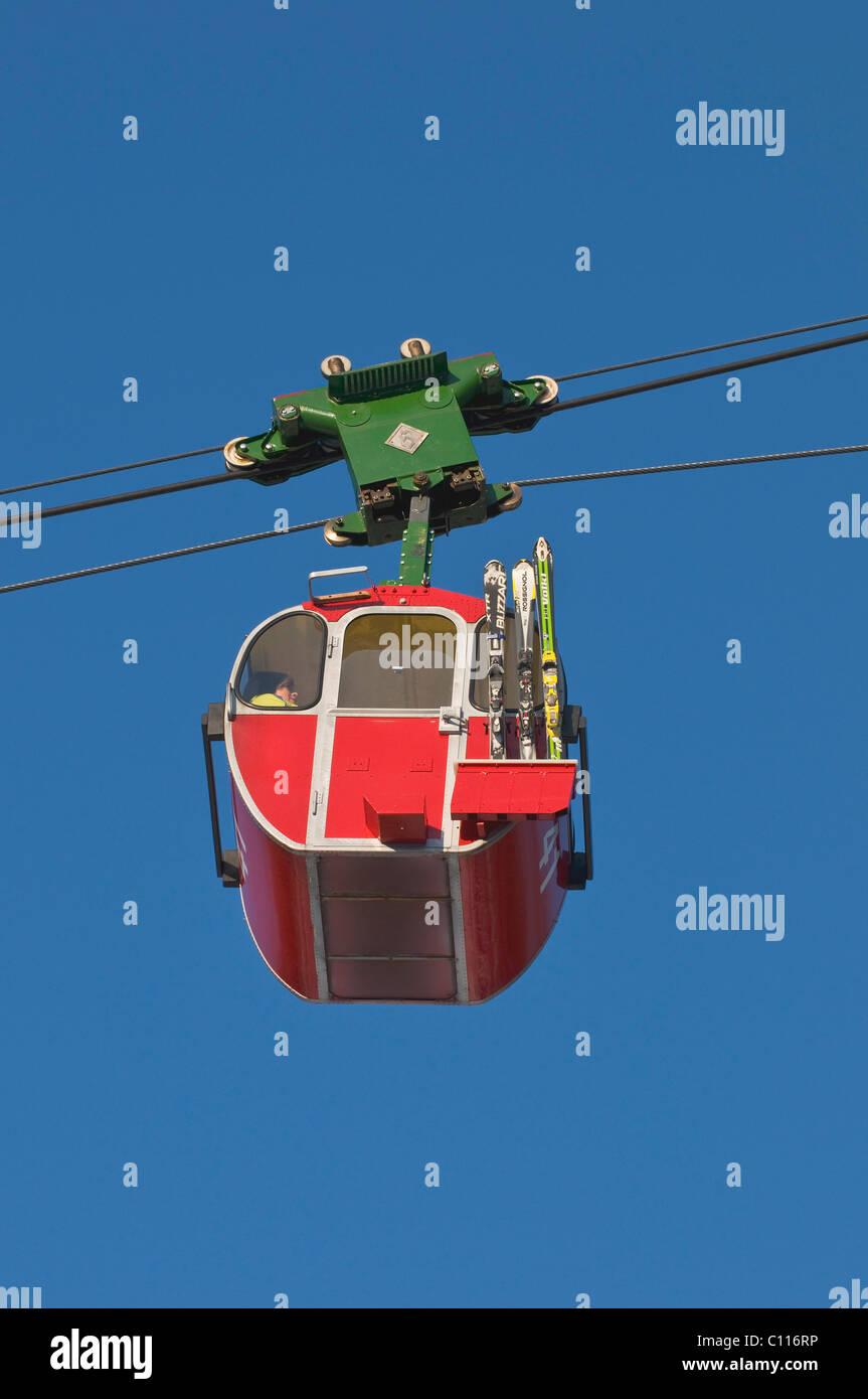 Cabina rosso del Kampenwandbahn funivia con gli sci sul lato esterno della cabina, salire la montagna, Chiemgau, Immagini Stock