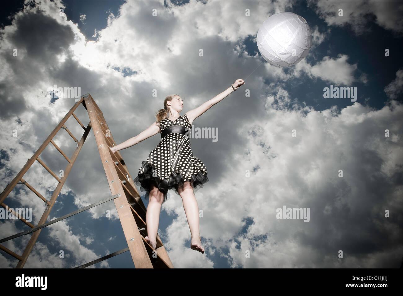 Una ragazza adolescente che indossa una in bianco e nero di polka abito punteggiata sorge su una scala mantenendo Immagini Stock
