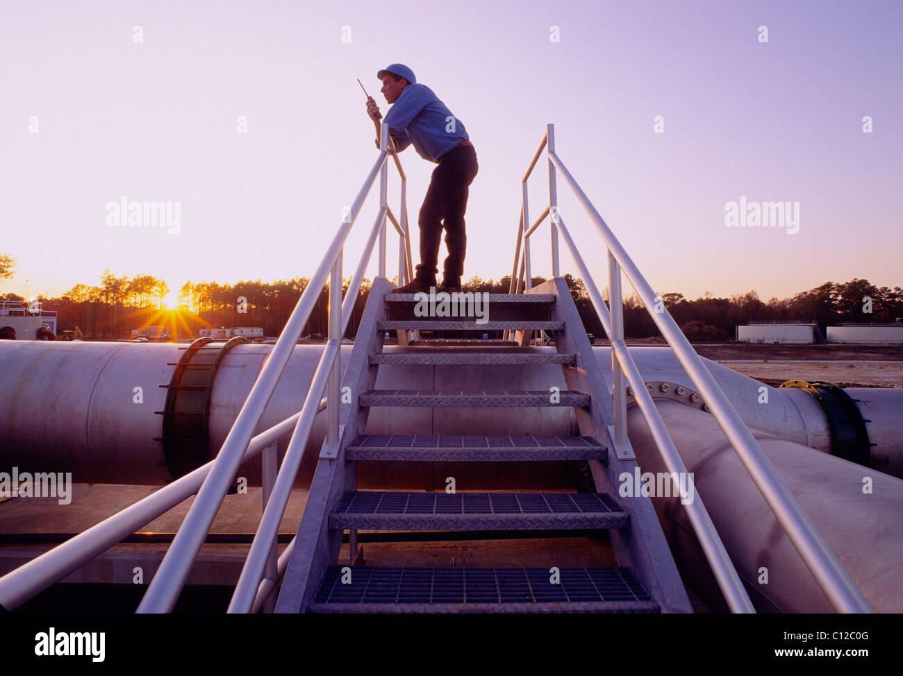 Tecnico su un walkie talkie radio al tramonto in un impianto di trattamento delle acque reflue, Houston, Texas, Immagini Stock