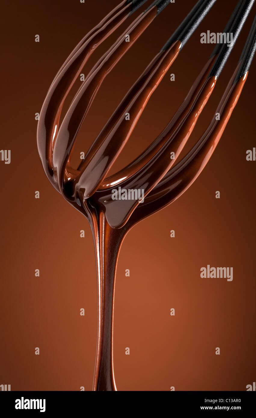 Cioccolato fondente il gocciolamento da una frusta Immagini Stock