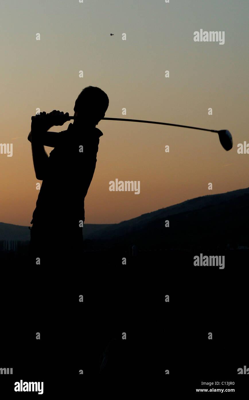 L uomo per giocare a golf con un paesaggio panoramico intorno a lui come il sole tramonta Immagini Stock