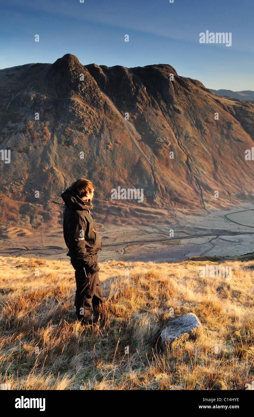 Walker su Bowfell affacciato sulla valle Mickleden e The Langdale Pikes su una chiara frosty mattina nel Lake District Immagini Stock