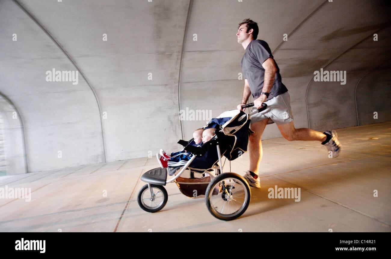 Un uomo che corre attraverso un tunnel con i suoi figli gemelli in un passeggino. (Sfocatura) Immagini Stock