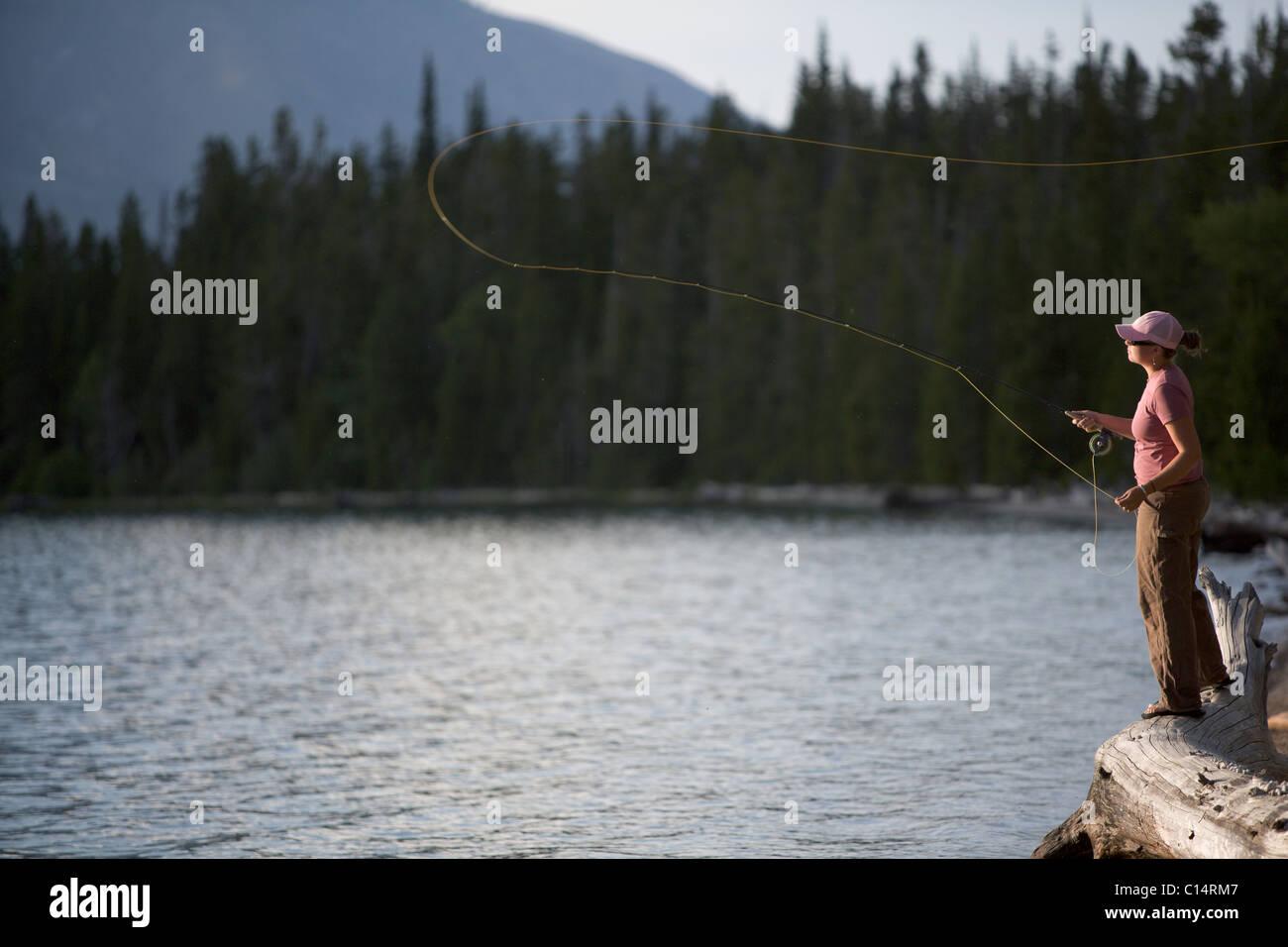 Una donna getta la sua flyline dalla riva di un lago. Immagini Stock