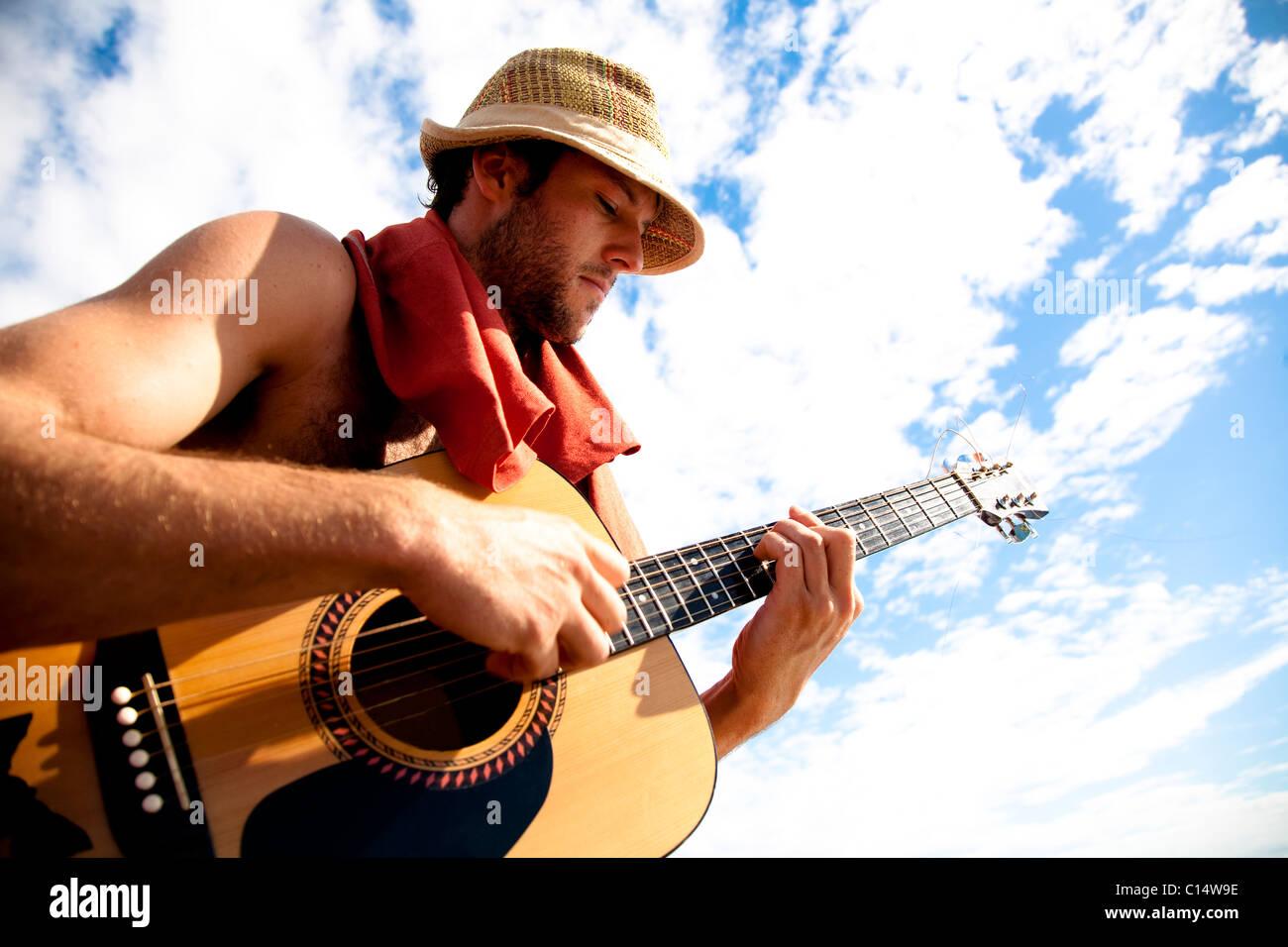 Un giovane uomo svolge la sua chitarra mentre su una barca da pesca al largo della costa della Malakati, Fiji. Immagini Stock