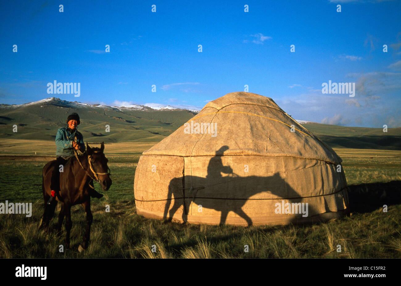 Cavallo e cavaliere di fronte una yurt, Moldo-Too Mountain Range, Song-Kul, Kirghizistan, Asia centrale Foto Stock
