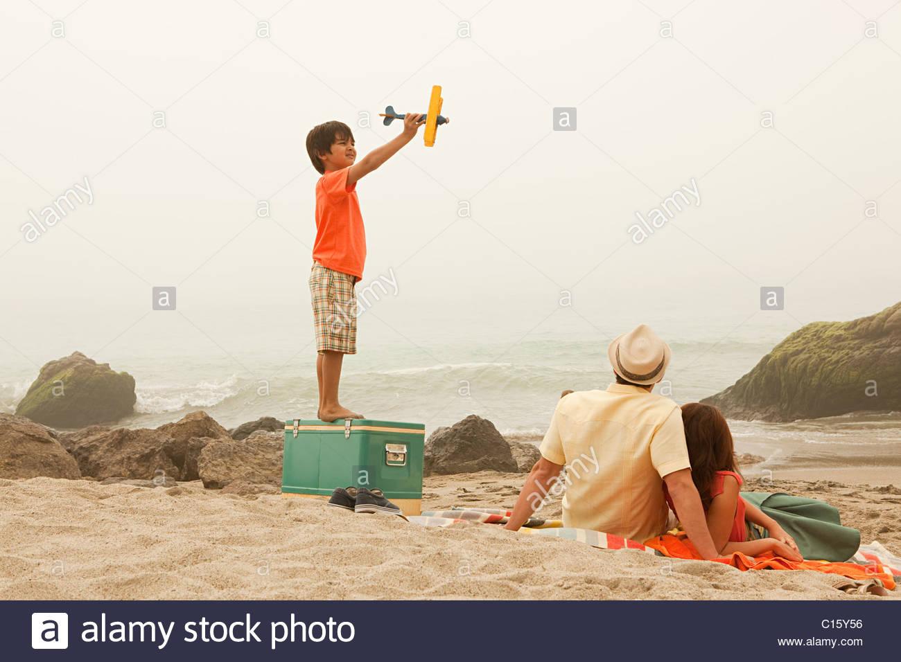 Famiglia sulla spiaggia, ragazzo giocando con Toy piano Immagini Stock