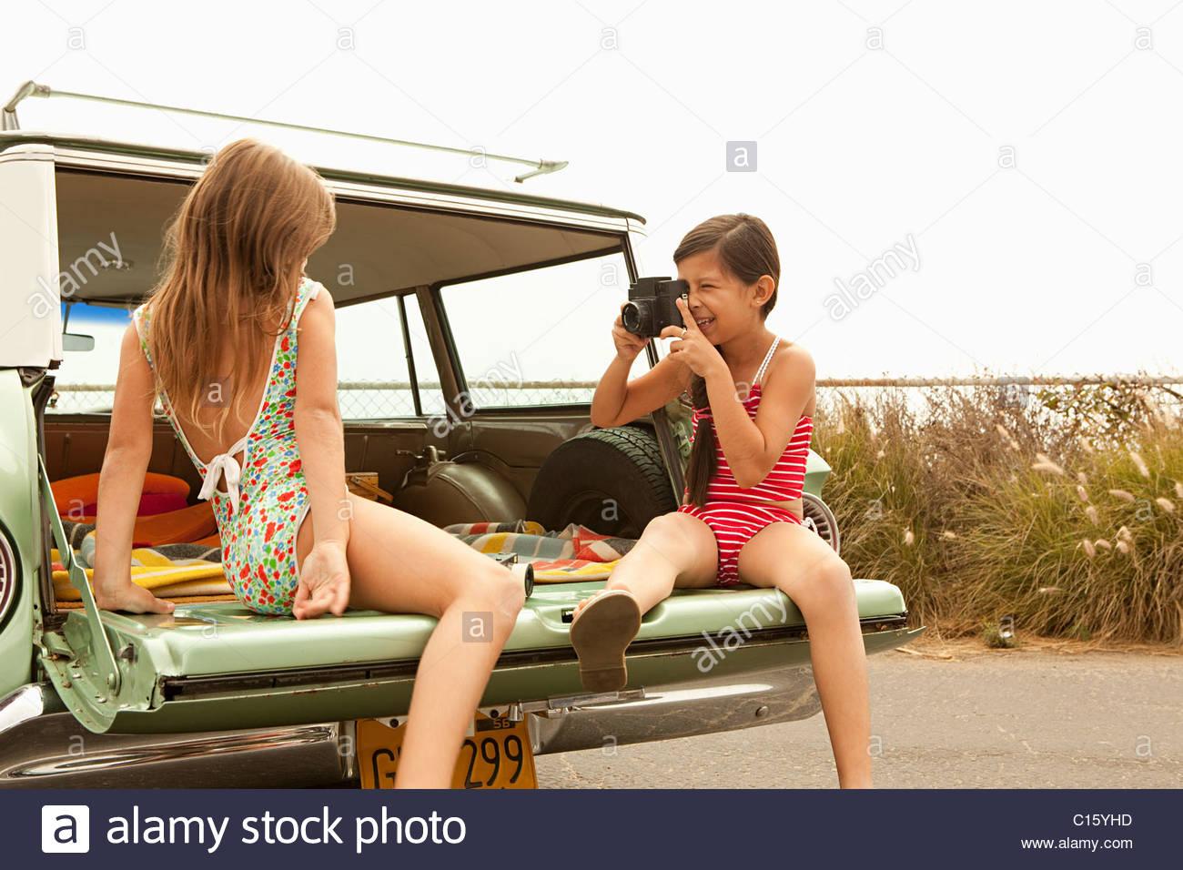 Due ragazze in seduta station wagon tenendo fotografia Immagini Stock