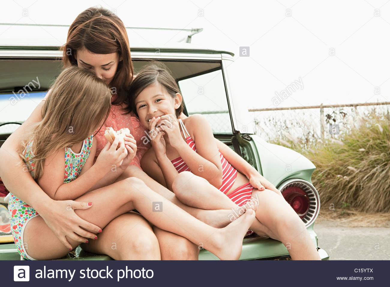 La madre e le figlie mangiando panini sul bagagliaio della vettura Immagini Stock