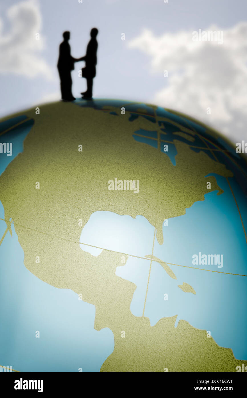 Toy figure agitare le mani sulla cima di un colorato globo di vetro in un international business Concetto di immagine. Immagini Stock