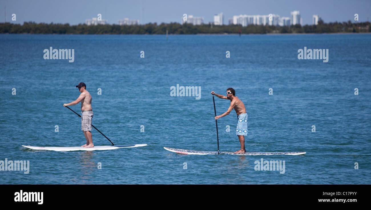Due uomini praticanti, paddleboard Miami Florida, Stati Uniti d'America Immagini Stock