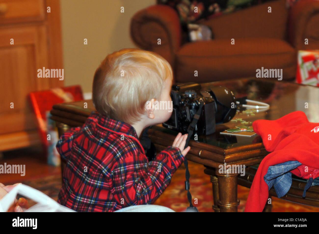 Ragazzo che guarda attraverso il mirino della fotocamera a Natale. Immagini Stock