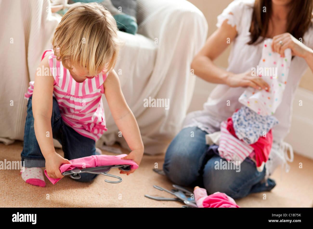 La madre e il bambino la scelta di vestiti da indossare Immagini Stock