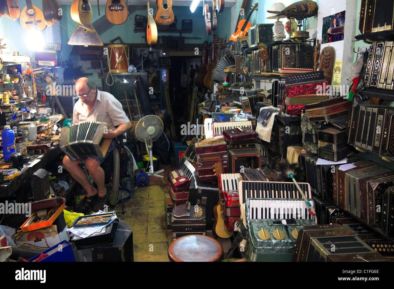 """""""Bandoneon Store': tango liutaio lavorando nel suo studio di Montevideo, Uruguay. Immagini Stock"""