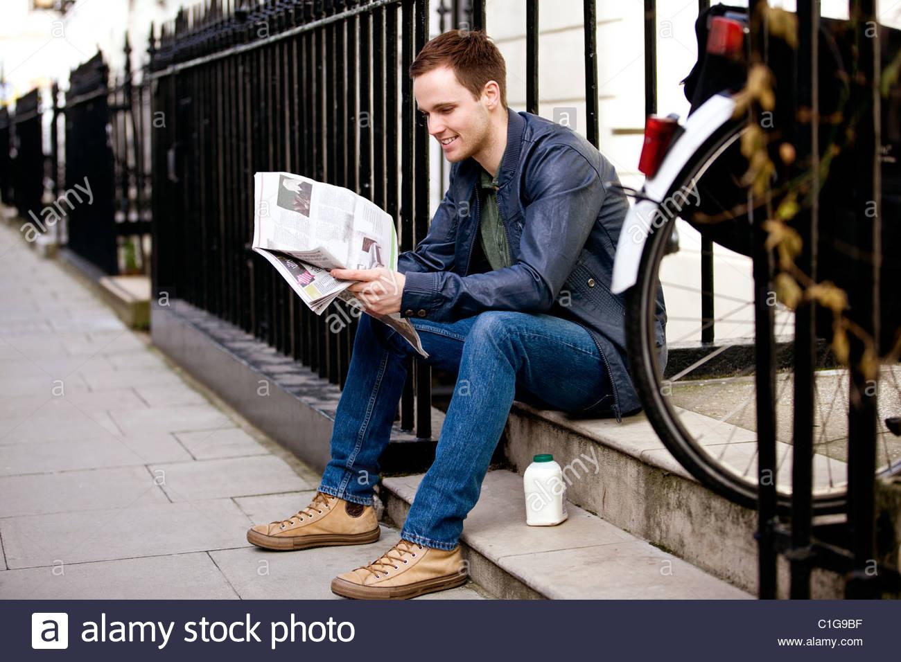 Un giovane uomo seduto su un gradino, leggendo un giornale Immagini Stock