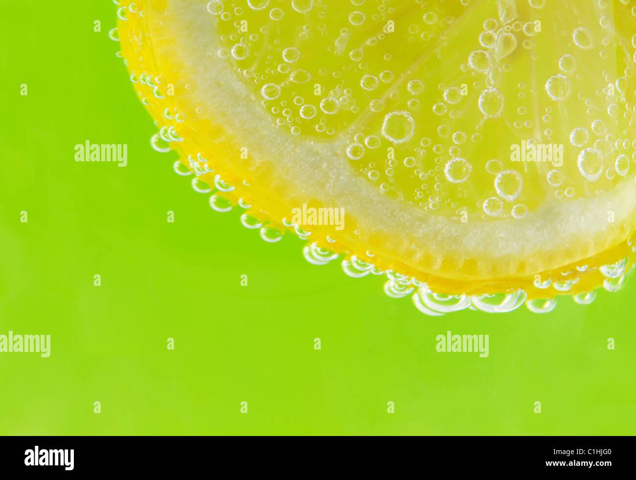 Una fetta di limone è accentato con seltzer bolle contro un fresco e verde primavera sfondo. Immagini Stock