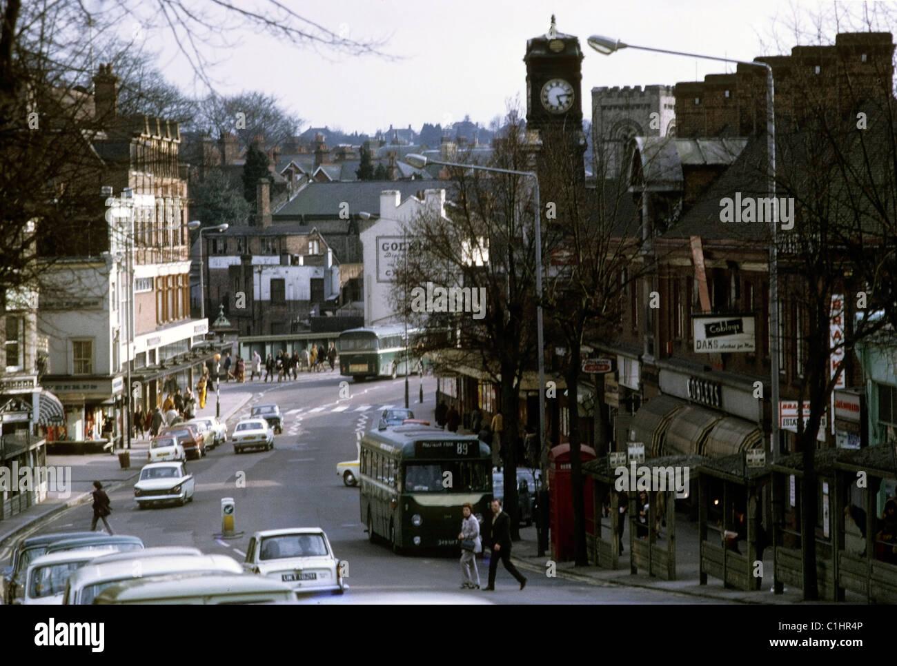 Anni Settanta vista storica di persone e di traffico sulla strada alta della città in autunno a Royal Tunbridge Immagini Stock
