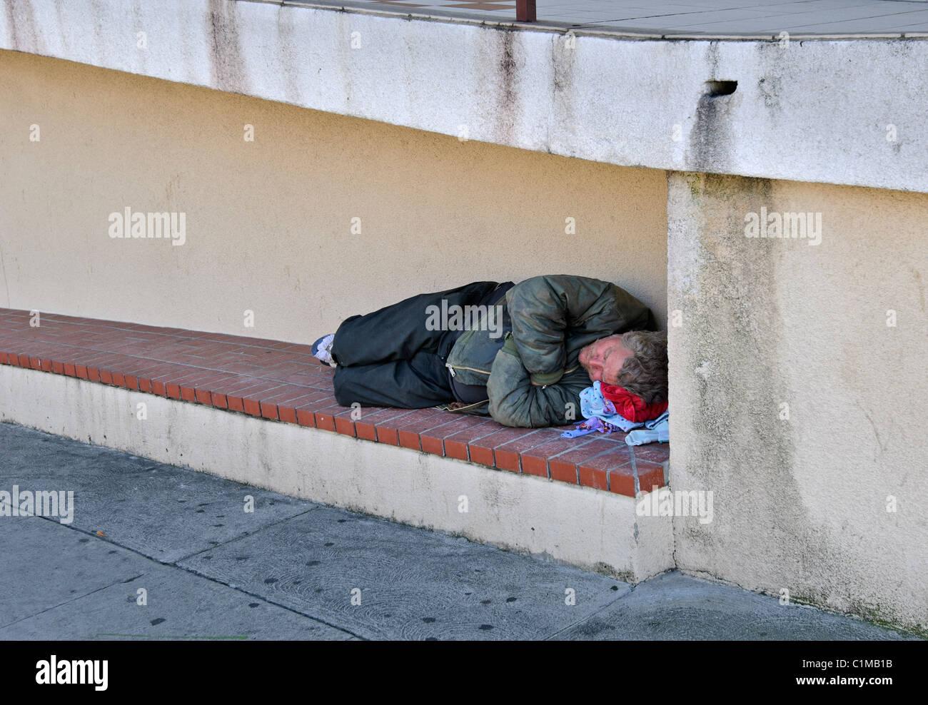 Un senzatetto dormire con una chiesa locale. Immagini Stock