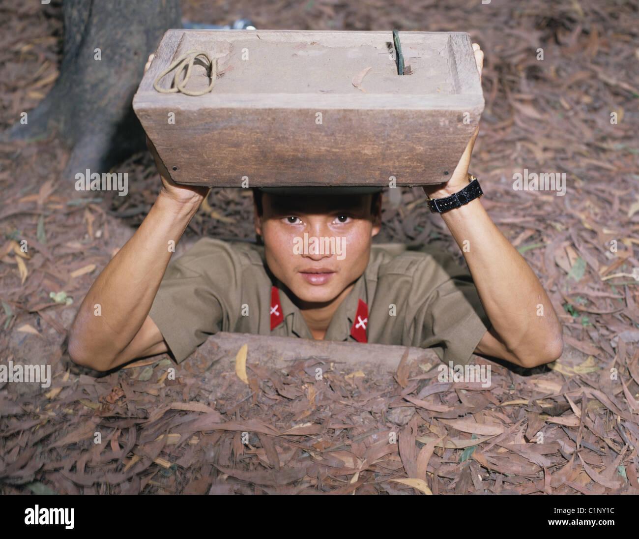 Soldato vietnamita guardando fuori da ingresso alla guerra del Vietnam tunnel. I Tunnel di Cu Chi. Ho Chi Minh city. Immagini Stock