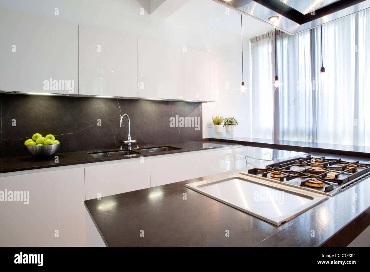 Moderno e di colore bianco lucido lucida cucina con contatore nero ...