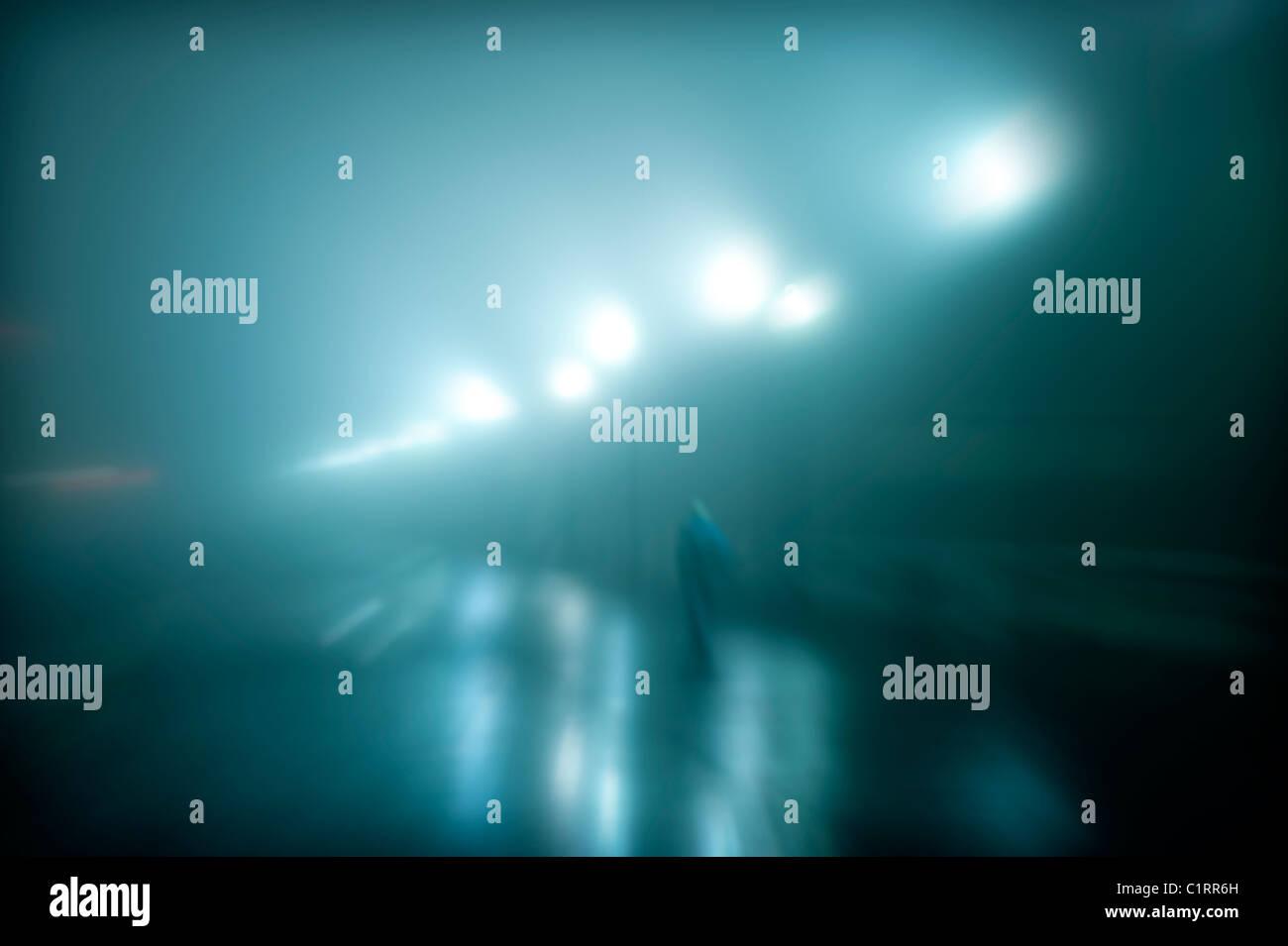 Figura misteriosa camminando su un wet notte di nebbia. Immagini Stock
