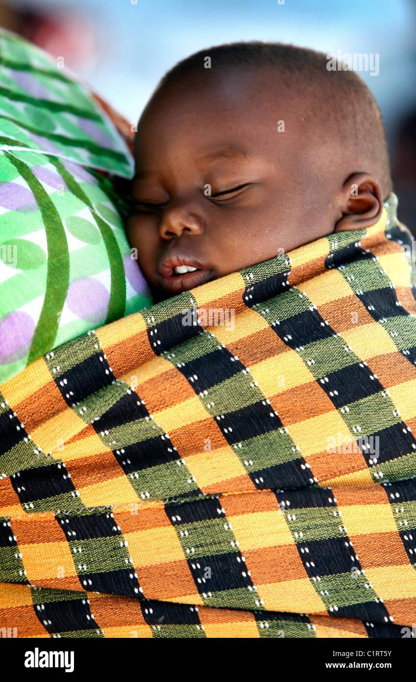 Bambino trasportato su madre torna, Senegal Africa Immagini Stock