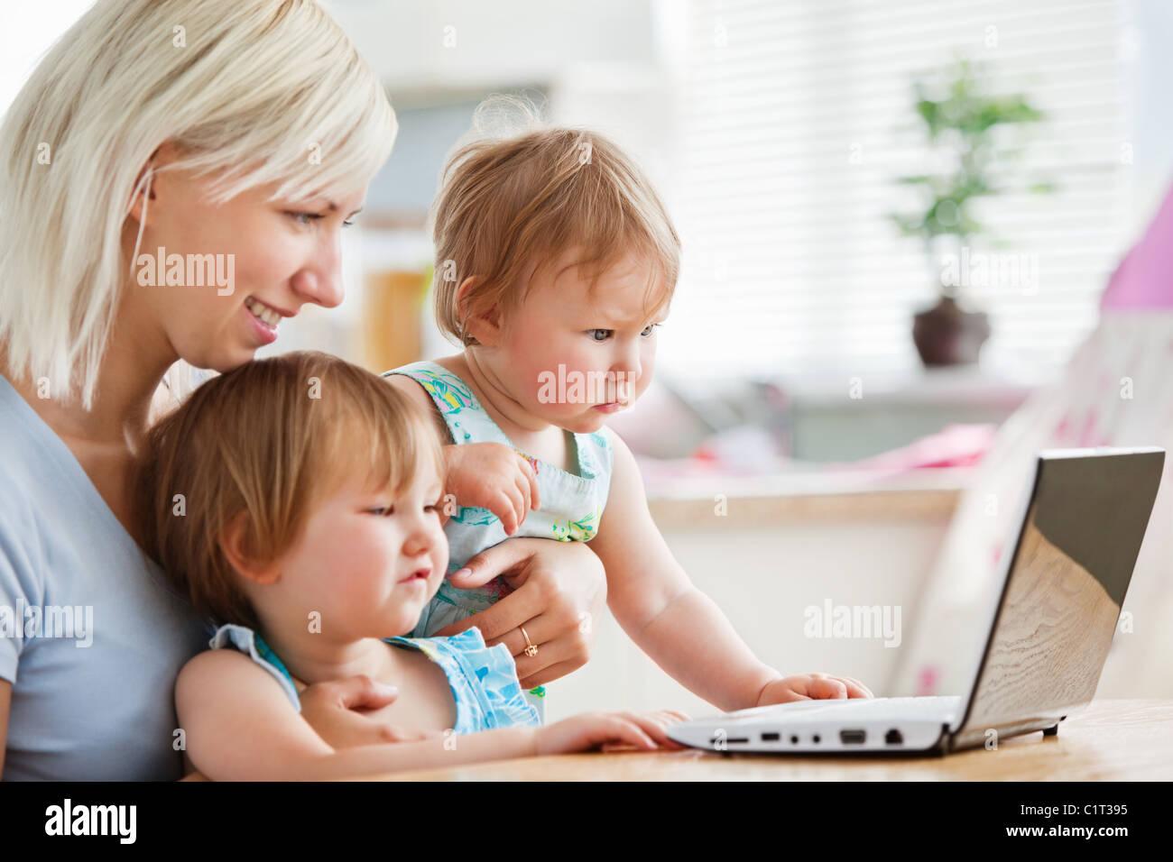 Stupito i bambini che guardano un notebook con la loro madre Immagini Stock
