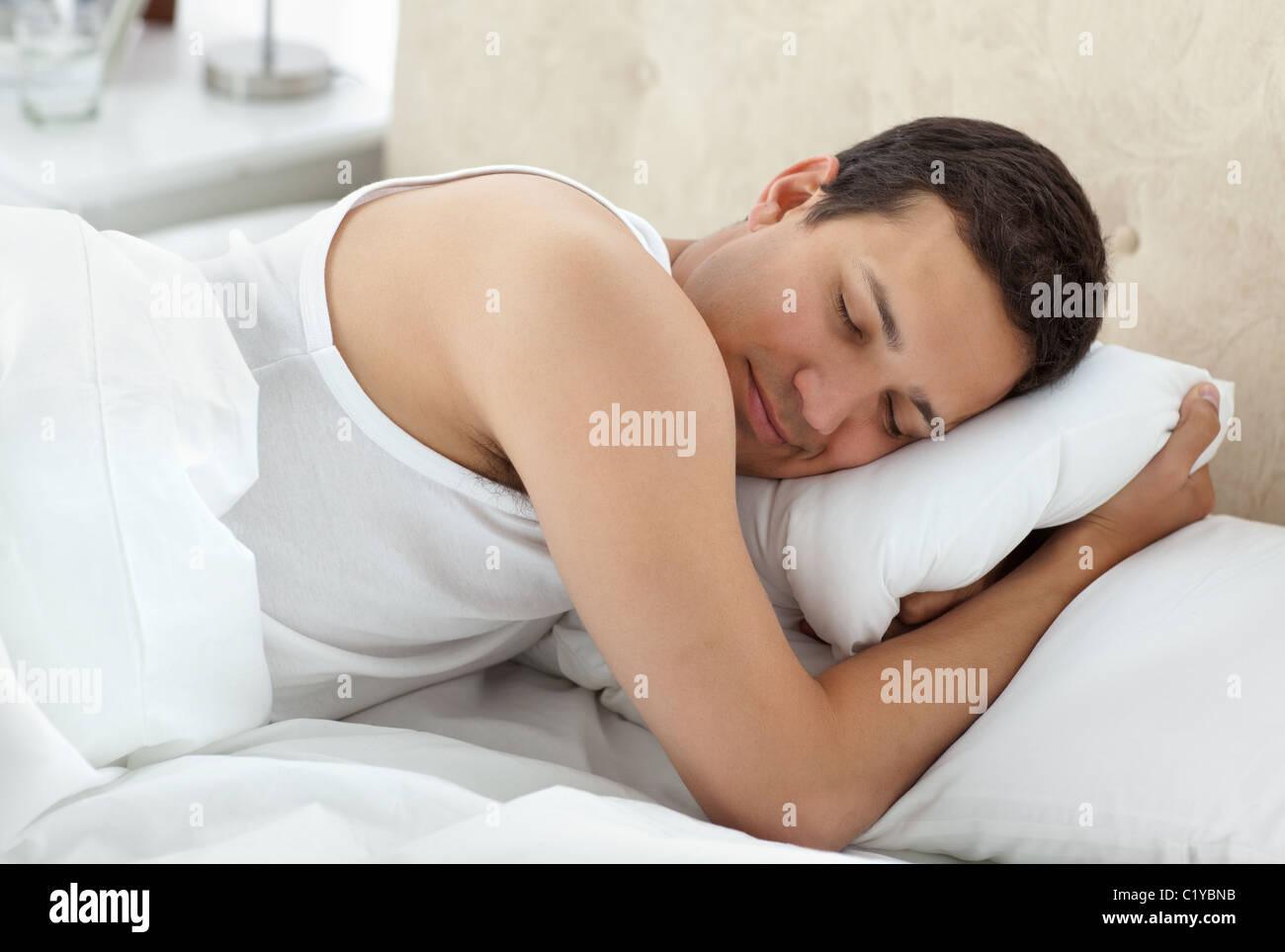 Carino uomo dorme tranquillamente sul suo letto Immagini Stock