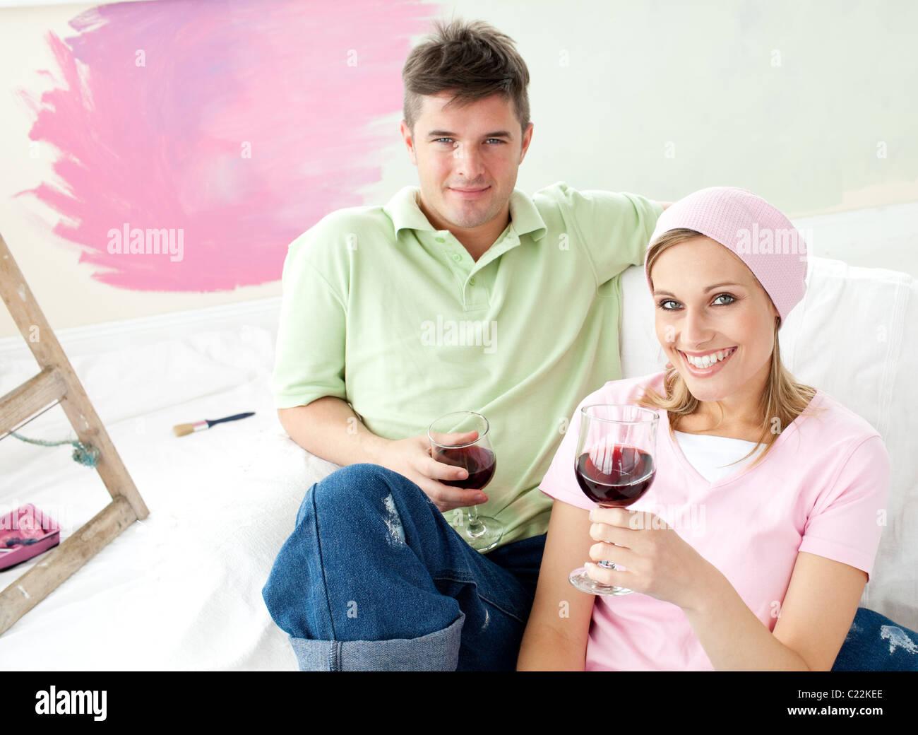 Felice coppia avente tempo libero insieme con un bicchiere di vino di sorridere alla telecamera Immagini Stock