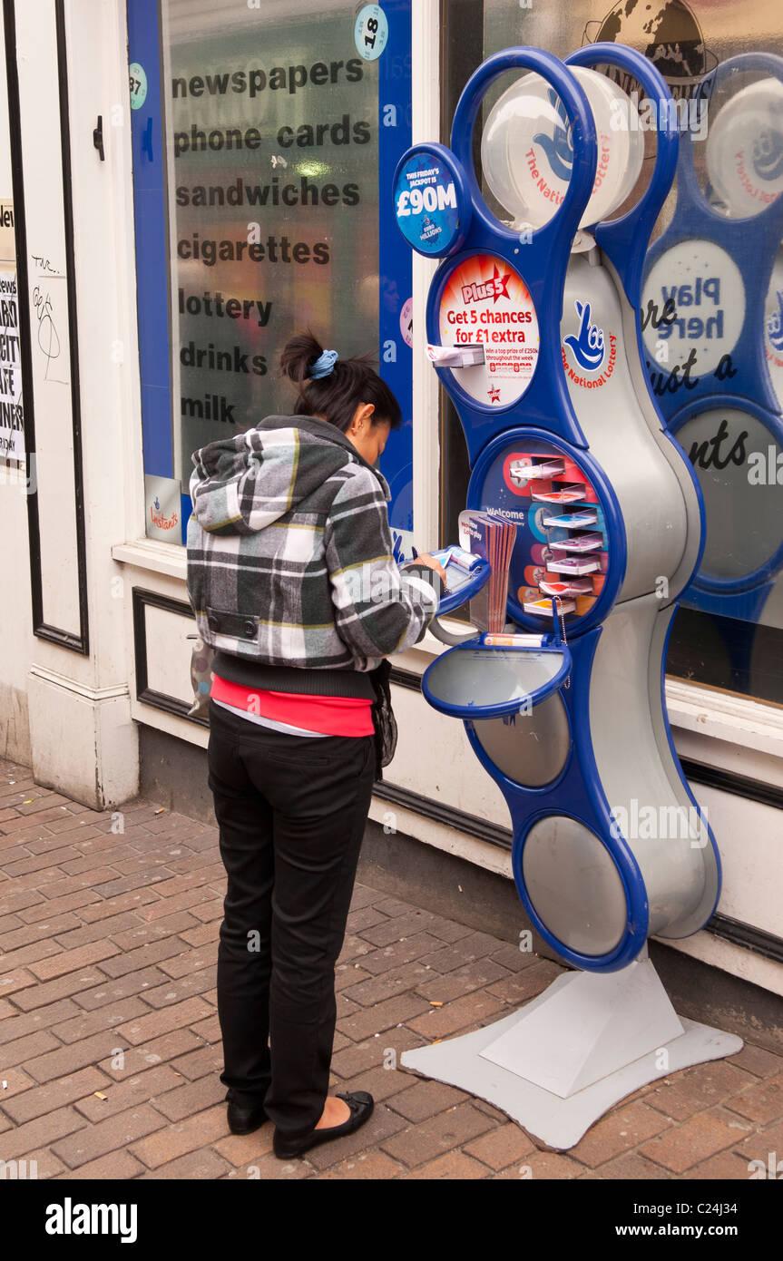 Una donna il riempimento in lei i biglietti della lotteria al di fuori di un negozio di Norwich , Norfolk , Inghilterra Immagini Stock