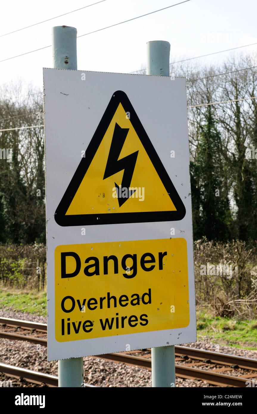 Pericolo cavi aerei sotto tensione segnale di avvertimento a fianco della linea ferroviaria, Harston, Cambridgeshire, Foto Stock