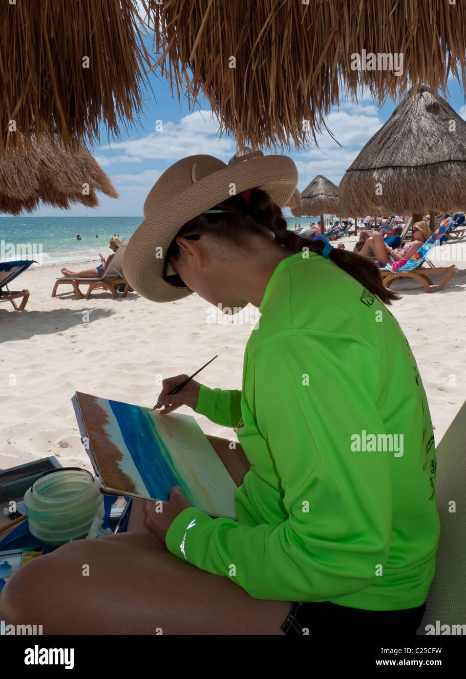 Una donna artista usa acquerelli di dipingere una scena sulla spiaggia di un resort sulla Riviera Maya in Messico Immagini Stock