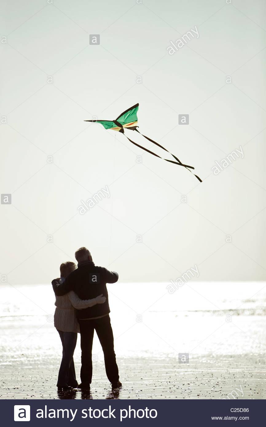 Una coppia senior volare un aquilone sulla spiaggia, vista posteriore Immagini Stock