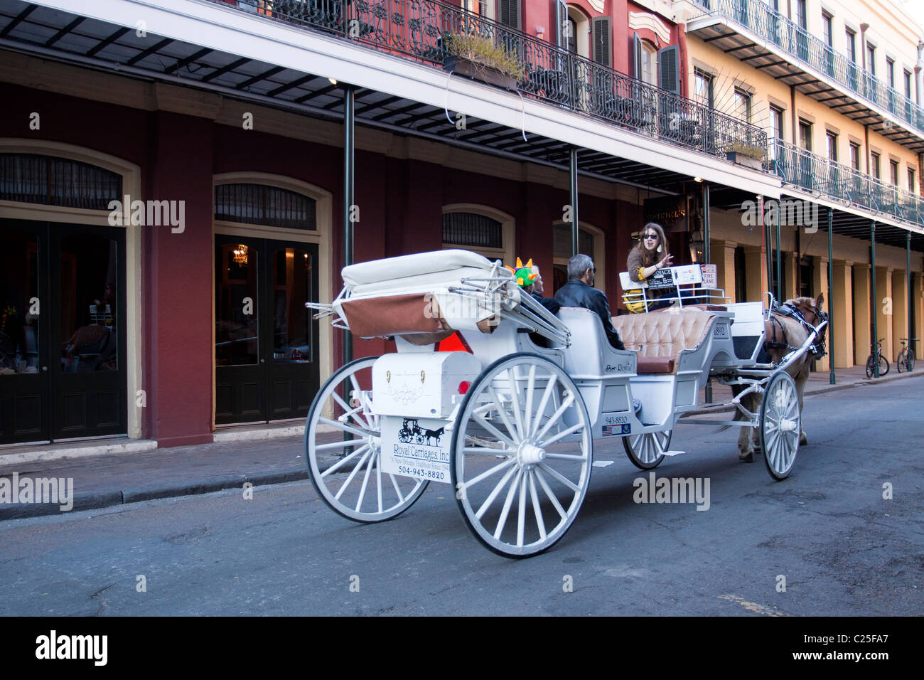 I turisti in sella a un cavallo bianco carrozza giù Chartres Street nel Quartiere Francese di New Orleans Immagini Stock