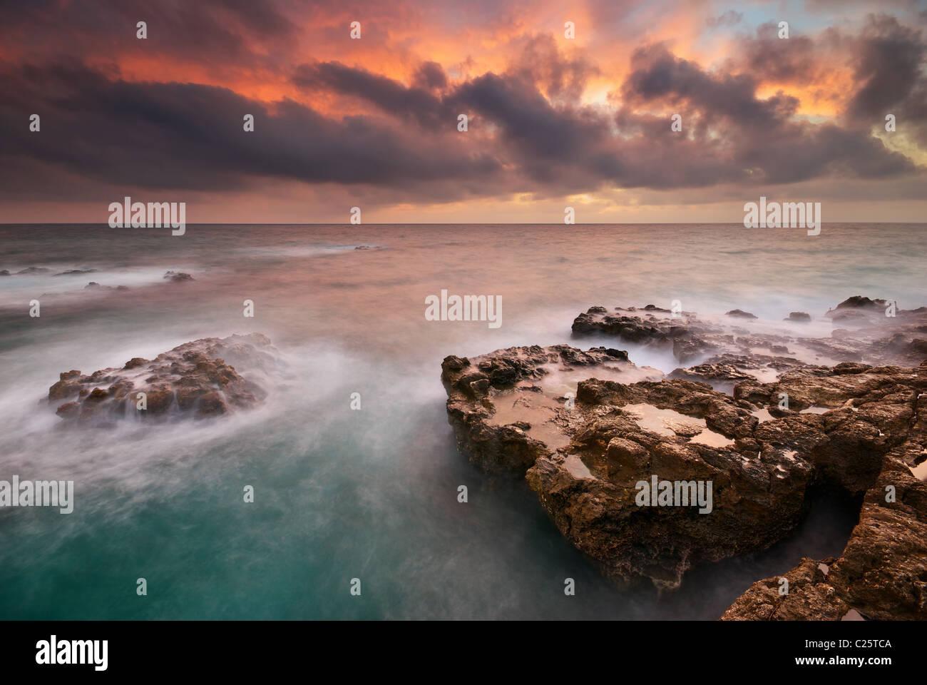 Bellissimo paesaggio marino. Il mare e la roccia al tramonto. La natura della composizione. Immagini Stock