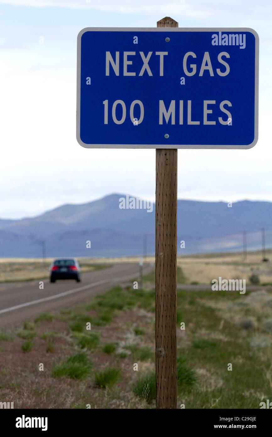 Gas successivo 100 miglia cartello stradale presso la Oregon/Nevada confine in McDermitt, STATI UNITI D'AMERICA. Immagini Stock
